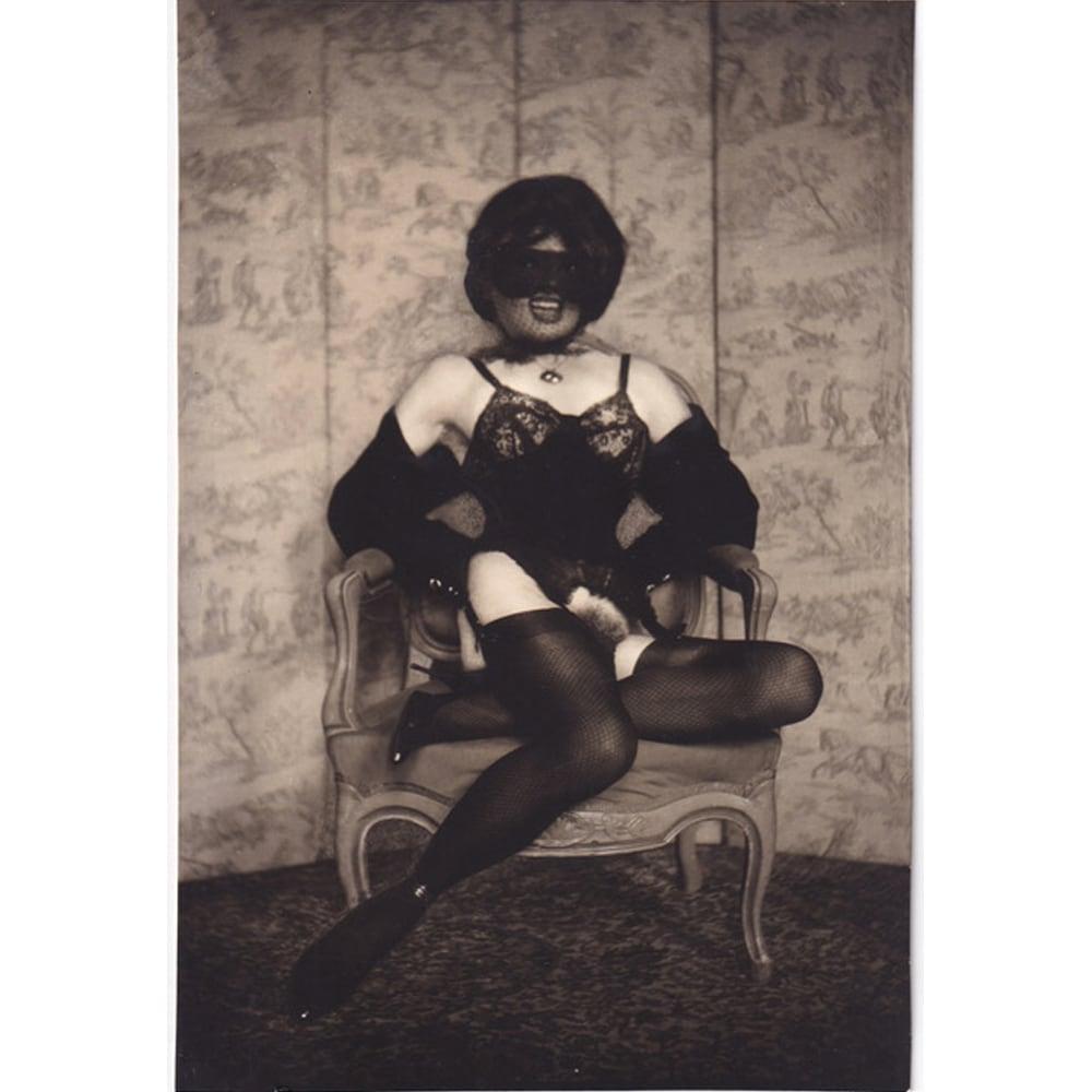 """Pierre Molinier """"Autoportrait assis, masque de poupée, loup, bas et talons hauts"""", circa 1965"""